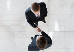 51091012 - directly above shot of businessmen shaking hands while standing on tiled floor in office